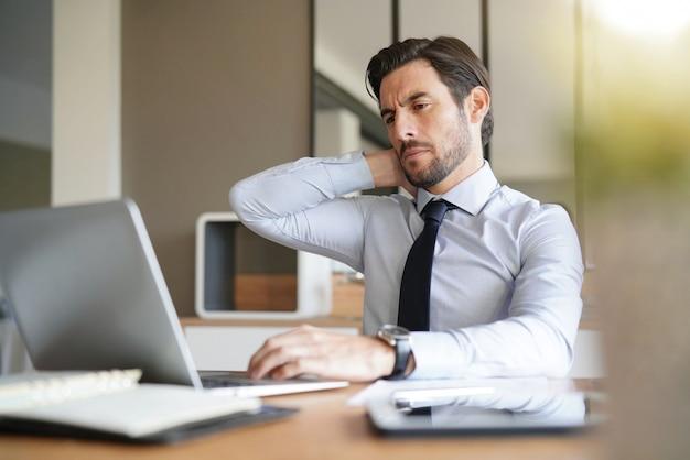 オフィスでラップトップを見てハンサムなビジネスマンを強調