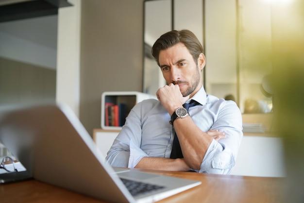 近代的なオフィスで働くリラックスした魅力的なビジネスマン