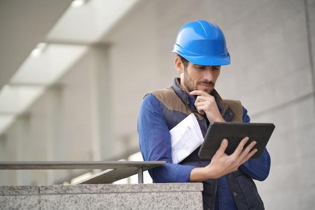 タブレットと青写真のヘルメット屋外でハンサムな建物の専門家