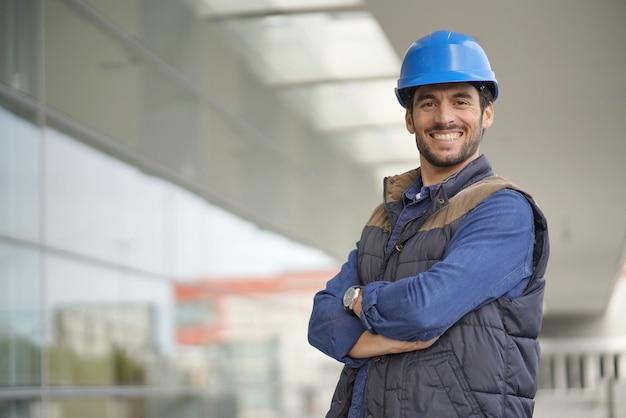 Усмехаясь промышленный работник в защитном шлеме перед современным зданием