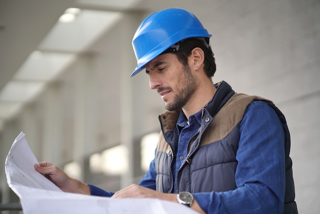 屋外の青写真をチェックヘルメットで魅力的な建築家