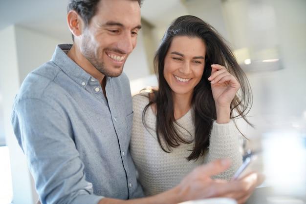 幸せなカップルが喜んで台所で携帯電話を見て