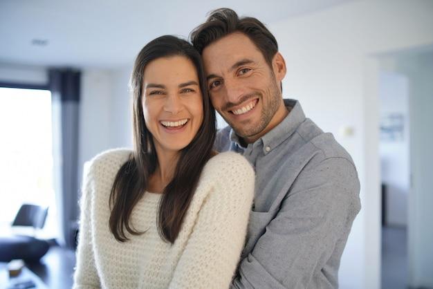 自宅で抱きしめるゴージャスなカップルの肖像画