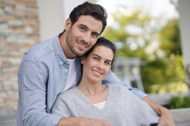 Портрет очень привлекательной пары, улыбаясь за пределами современного дома