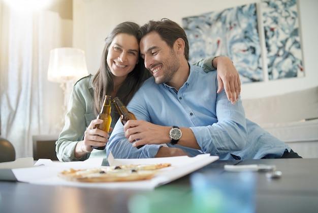 Счастливая расслабленная пара, разделяющая пиццу дома