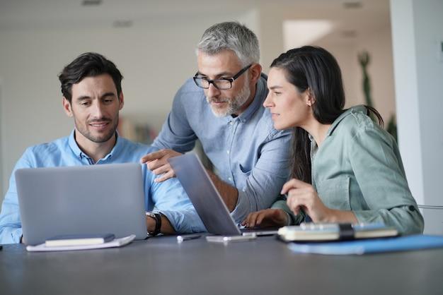コンピューターを扱う上司と若い同僚
