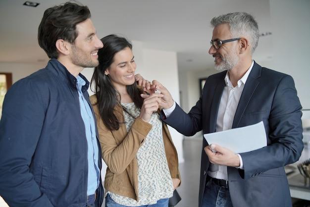 モダンな家の中で契約を見て不動産業者とカップルします。