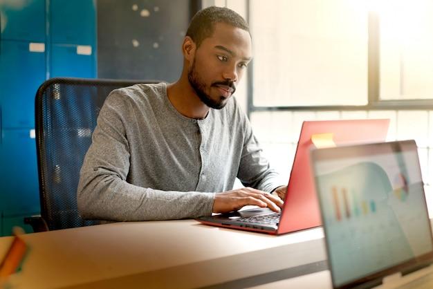 Молодой черный человек, работающий в современных офисных помещениях