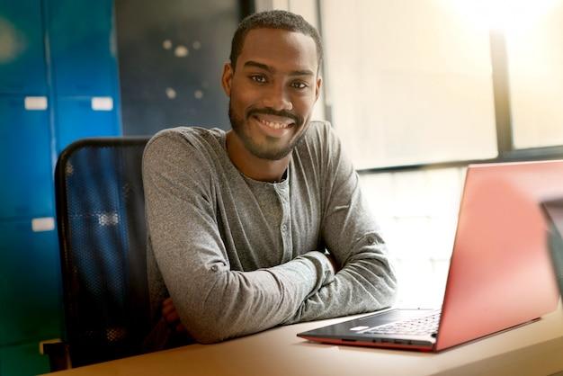 近代的なオフィススペースで働く若い黒人男性