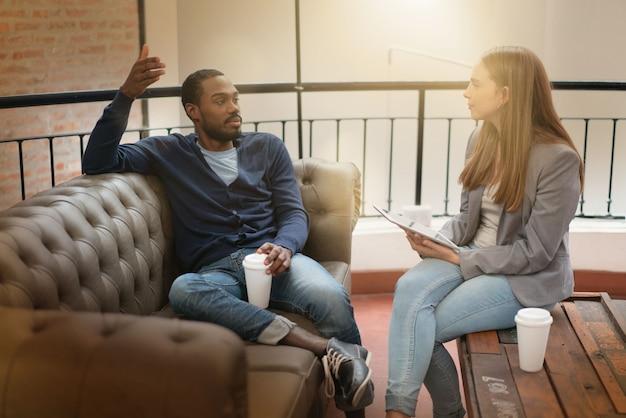 現代の職場のソファの上のアイデアをカジュアルに議論する労働者