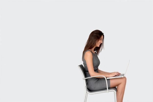 ノートパソコンの前の椅子に座っている女性実業家