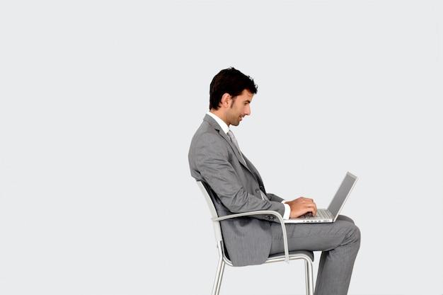 ノートパソコンの前の椅子に座っている実業家