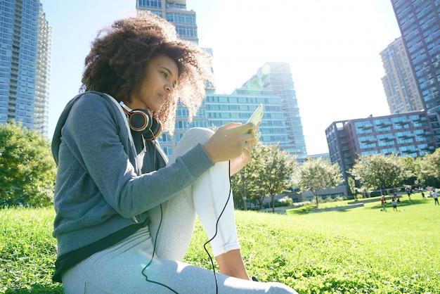 スマートフォンで音楽を聴く公園で混血の少女の肖像画