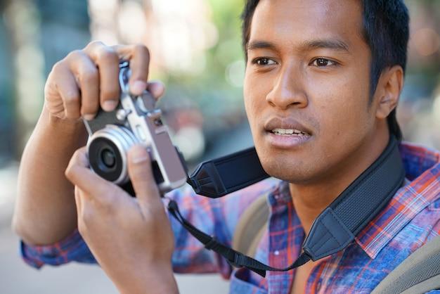 若い男がニューヨークの近所で写真を撮る