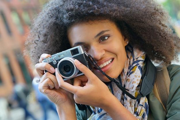 カメラで写真を撮るニューヨーク市でトレンディな女の子