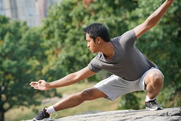 Человек делает упражнения боевого искусства в центральном парке