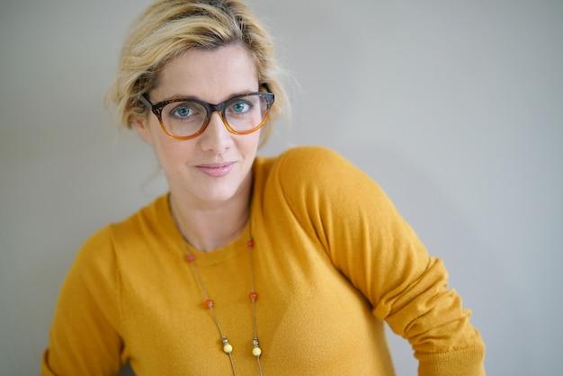 眼鏡と黄色のシャツと美しい金髪の女性