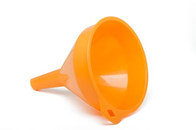 白い背景に分離されたオレンジ色のプラスチック漏斗のビューを閉じます。