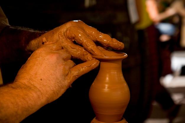 新しい作品に取り組んでいる陶工の手のクローズアップ表示。