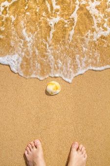 シェルと男性の足を入浴海岸の波のクローズアップ表示。
