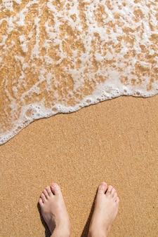 男性の足を入浴海岸の波のビューを閉じます。