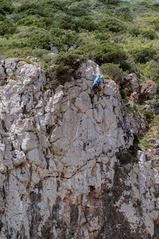 男は崖を登る