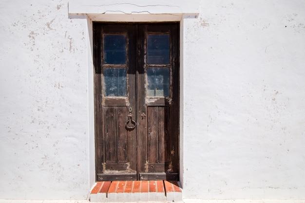 白い家から古い木製のドアのビューを閉じます。