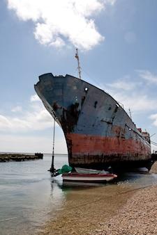 海岸線に停まっている古くてさびた船の景色。