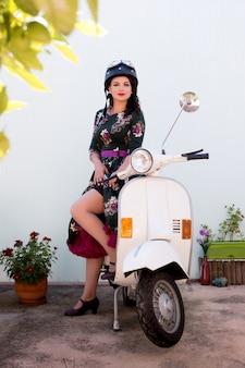 オートバイの横にあるビンテージの女の子