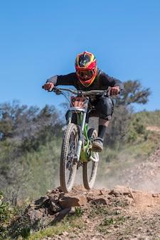 下り坂の競争、バイカーは田舎で速く跳びます。