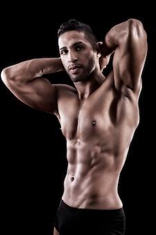 黒の背景に筋肉質の男
