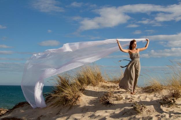 長く美しい白い布とビーチで美しい少女