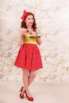 カラフルなカップケーキのトレイを持って美しいピンナップ赤毛の女の子のビュー。