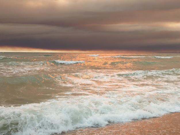 ポルトガル、ヴィラモウラの暗い雲とビーチに沈む夕日。