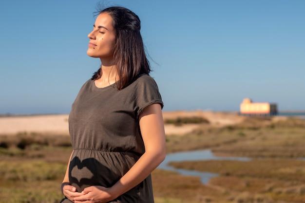 妊娠中の女性が湿地でポーズします。