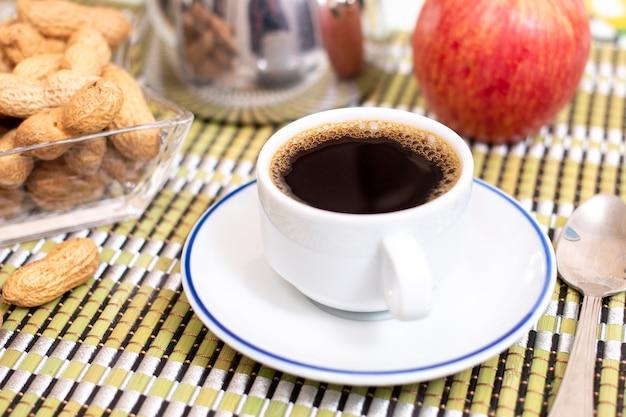 Чашка кофе эспрессо с арахисом и фруктами