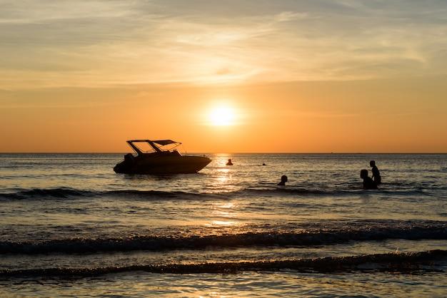 人々はシャドーボートの近くで泳ぎ、ビーチでは軽い夕日