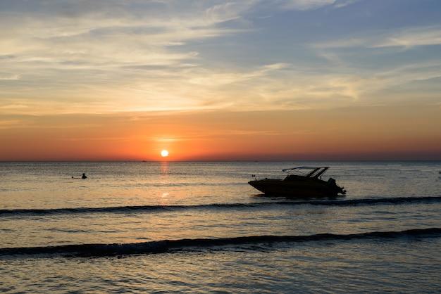夕日と海のボートの影