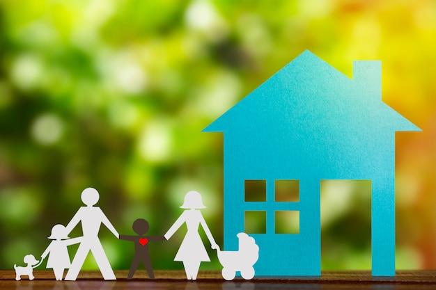子供と里親の黒人の息子と手を繋いでいるカップルの紙の図。青い家と背景をぼかした写真。多様性、マイノリティの概念。