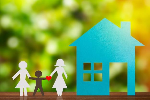 里子と手を繋いでいる同性愛者のカップルの紙図。青い家と破壊された背景。多様性、マイノリティの概念。