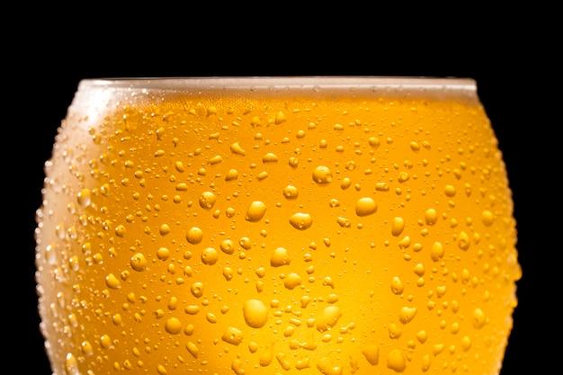 滴と泡で冷たいビールのクローズアップ