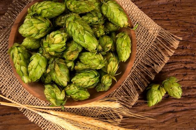木製の背景に木製のボウルと小麦の耳でビール醸造成分ホップコーン。ビール醸造所のコンセプトです。