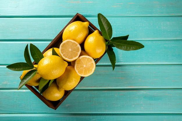 Деревянная коробка с лимонами на зеленом фоне деревянных