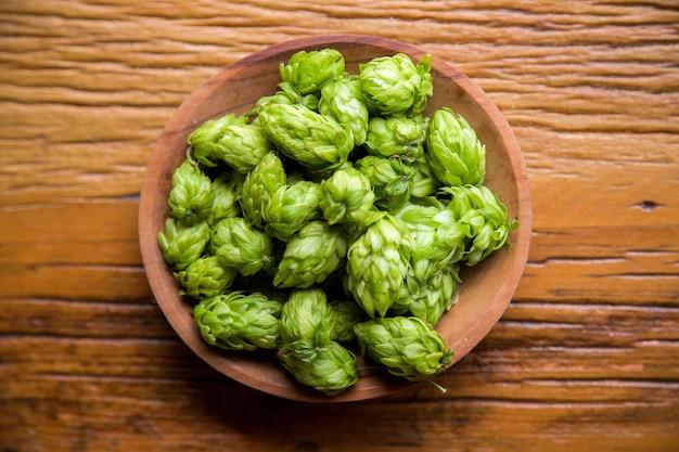 Ингридиенты пивоварения пива шишки хмеля в деревянных ушах шара и пшеницы на деревянной предпосылке. концепция пивоваренного завода.