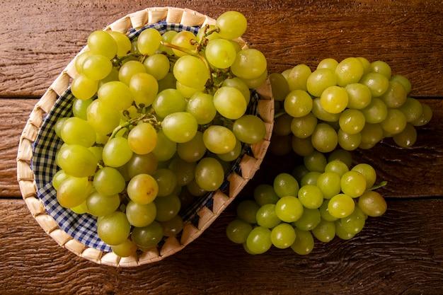 Гроздь зеленого винограда в корзине, плоды осени, символ изобилия на деревенском фоне дерева с копией пространства, вид сверху, крупным планом