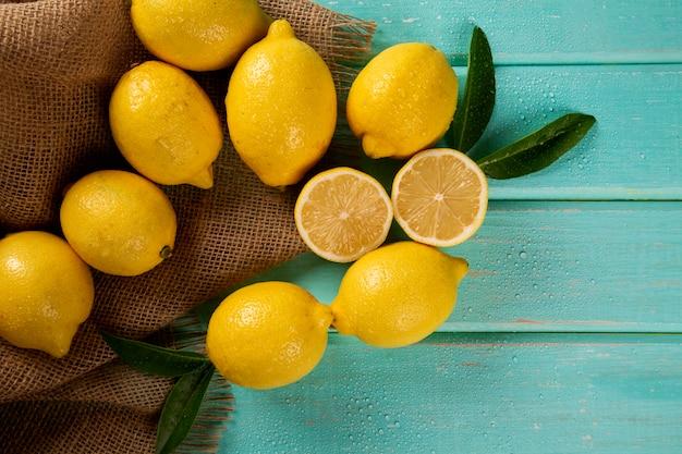 Желтые лимоны на зеленом фоне деревянных