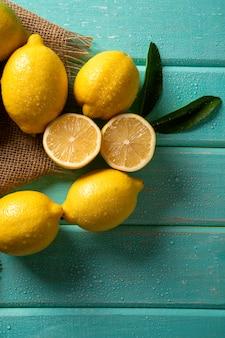 緑の木製の背景に黄色のレモン