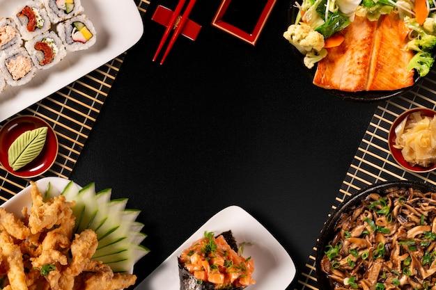 Японская пищевая композиция. различные виды суши размещены на доске черный камень. острый салат кимчи, палочки для еды и миска соевого соуса.