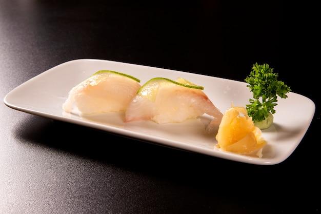 Суши нигири широми с белой рыбой на черном фоне