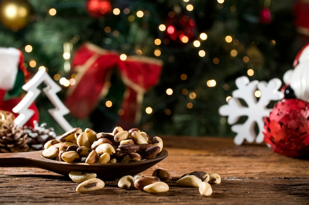 ブラジルのナッツ:カスタニャは、クリスマス背景をぼかしたボード上のボウルにパラを行います